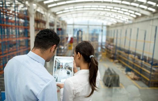 Business couple working on freight transportation and using a tablet computer to check stock at a warehouse